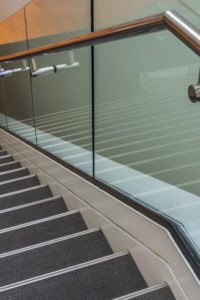 Stairs are leading downward to a small platform. The stair steps are gray. A metal handrail and glass panels are next to the stairs.